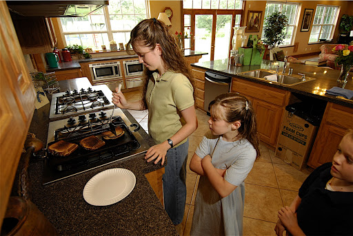 Picture of Michelle Duggar using one of her cooktops to make sandwhiches.