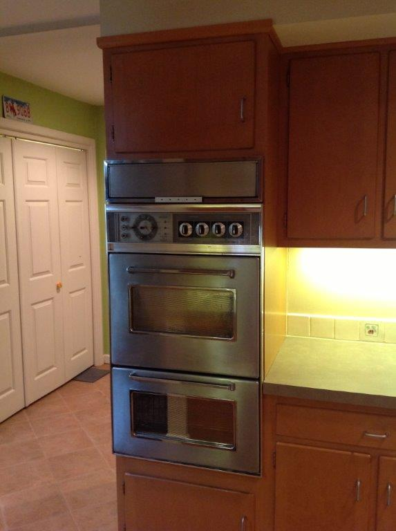 Picture of old stainless steel double-oven in wooden cabinet