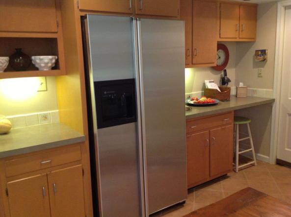 Older model stainless steel refrigerator sitting proud of the cabinets surrounding.